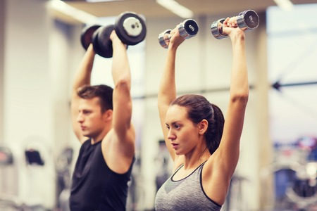 Foto de sport, fitness, lifestyle and people concept - smiling man and woman with dumbbells flexing muscles in gym - Imagen libre de derechos