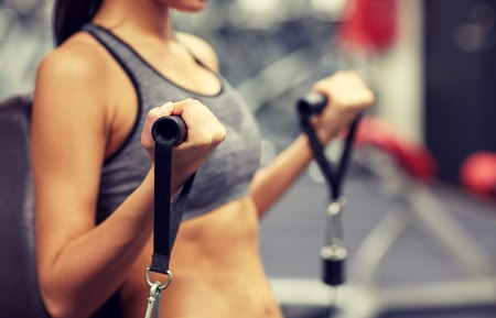 Photo pour sport, fitness, lifestyle and people concept - close up of young woman flexing muscles on cable gym machine - image libre de droit