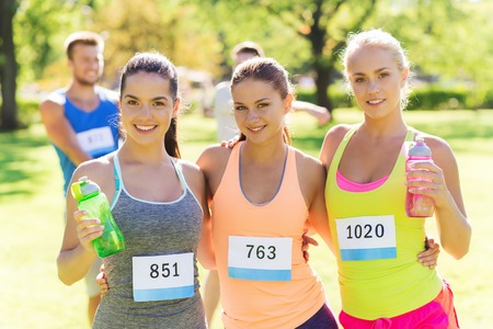 fitness, sport, friendship, marathon and healthy lifestyle concept - happy young sporty women with racing badge numbers and water bottles outdoors