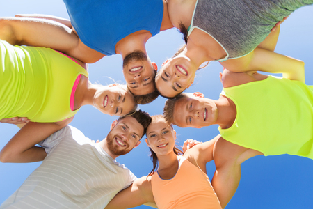 Foto de fitness, sport, friendship and healthy lifestyle concept - group of happy teenage friends or sportsmen in circle outdoors - Imagen libre de derechos