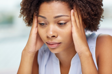 Foto de people, emotions, stress and health care concept - unhappy african american young woman touching her head and suffering from headache - Imagen libre de derechos