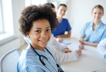 Photo for health care, profession, people and medicine concept - happy african american female doctor or nurse over group of medics meeting at hospital - Royalty Free Image