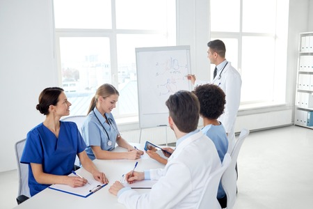 Photo pour medical education, health care, medical education, people and medicine concept - group of happy doctors or interns with mentor meeting and drawing on flip board at hospital - image libre de droit