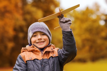 Photo pour autumn, childhood, dream, leisure and people concept - happy little boy playing with wooden toy plane outdoors - image libre de droit