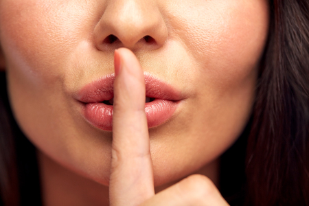 Photo pour silence, gesture and beauty concept - close up of young woman holding finger on lips - image libre de droit