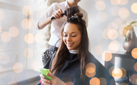 Foto de beauty, hairstyle and people concept - happy young woman with smartphone and hairdresser making hair styling at salon over holidays lights - Imagen libre de derechos