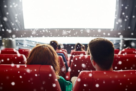 Photo for cinema, entertainment, leisure and people concept - couple watching movie in theater from back over snowflakes - Royalty Free Image