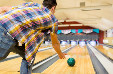 Photo pour people, leisure, sport and entertainment concept - close up of young man throwing ball to alley in bowling club - image libre de droit