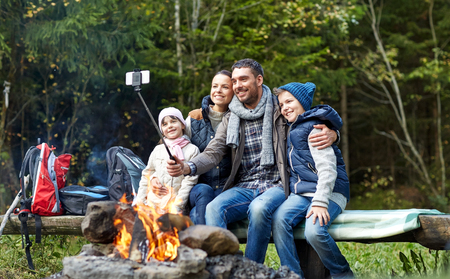 Foto de camping, travel, tourism, hike and people concept - happy family sitting on bench and taking picture with smartphone on selfie stick at campfire in woods - Imagen libre de derechos