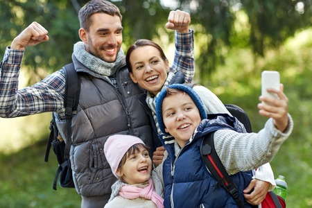 Foto de travel, tourism, hike, technology and people concept - happy family with backpacks taking selfie by smartphone in woods - Imagen libre de derechos