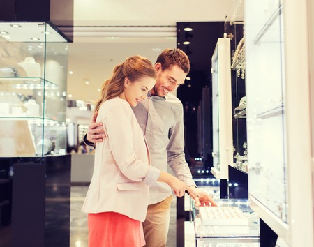 Photo for sale, consumerism, shopping and people concept - happy couple choosing engagement ring at jewelry store in mall - Royalty Free Image