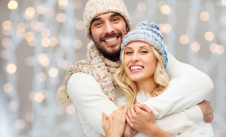 Foto de winter, fashion, couple, christmas and people concept - smiling man and woman in hats and scarf hugging over holidays lights background - Imagen libre de derechos