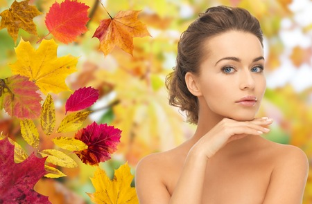 Foto de beauty, people, season and health concept - beautiful young woman touching her face over autumn leaves background - Imagen libre de derechos