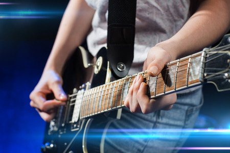 Photo for music, people, musical instruments and entertainment concept - close up female musician hands playing electric guitar with mediator - Royalty Free Image