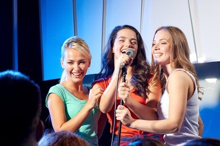 Photo for bachelorette party, karaoke, music concert and holidays concept - three happy young women or girls band singing on night club stage - Royalty Free Image