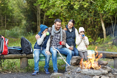 Photo pour camping, travel, tourism, hike and people concept - happy family sitting on bench and drinking hot tea from cups at camp fire in woods - image libre de droit