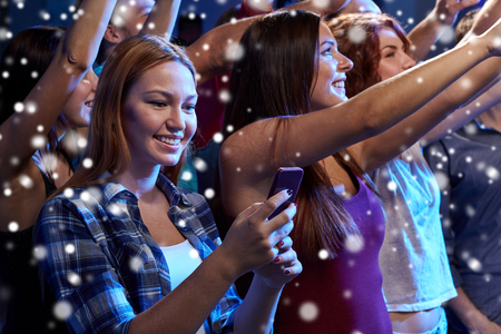 Photo for party, holidays, celebration, nightlife and people concept - smiling young woman with smartphone texting message at concert in club and snow effect - Royalty Free Image