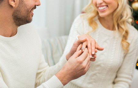 Photo for love, couple, relationship and holidays concept - happy man giving diamond ring to woman for christmas - Royalty Free Image
