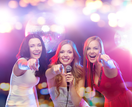 Photo for party, holidays, nightlife, entertainment and people concept - concept - happy women with microphone singing karaoke and pointing finger on you at night club - Royalty Free Image