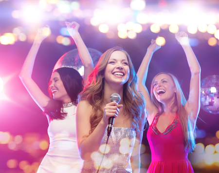 Photo for party, holidays, nightlife, entertainment and people concept - concept - happy women with microphone singing karaoke and dancing at night club - Royalty Free Image