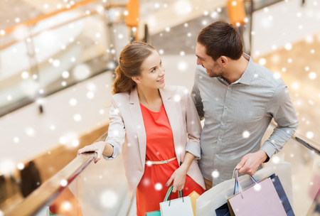Foto für sale, consumerism and people concept - happy young couple with shopping bags rising on escalator and talking and raising on escalator in mall with snow effect - Lizenzfreies Bild