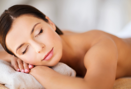 Photo pour health and beauty, resort and relaxation concept - beautiful woman with closed eyes in spa salon lying on the massage desk - image libre de droit