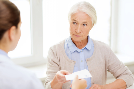 Photo for medicine, age, health care and people concept - doctor giving prescription to senior woman at hospital - Royalty Free Image
