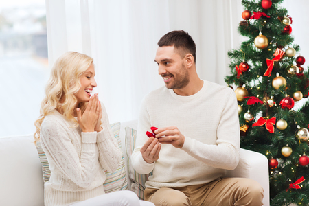 Photo for love, christmas, couple, proposal and people concept - happy man giving engagement ring in little red box to woman at home - Royalty Free Image