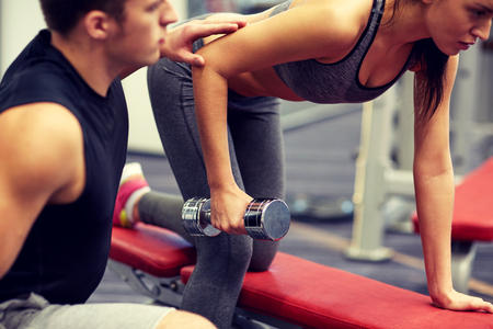 Foto de fitness, sport, exercising and weightlifting concept - close up of young woman and personal trainer with dumbbells flexing muscles in gym - Imagen libre de derechos