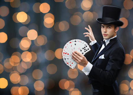 Foto de magic, gambling, casino, people and show concept - magician in top hat showing trick with playing cards over nigh lights background - Imagen libre de derechos