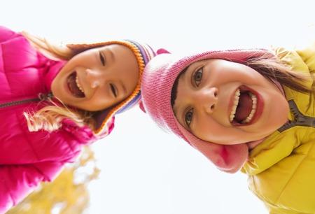 Foto de childhood, leisure, friendship and people concept - happy laughing girls faces outdoors - Imagen libre de derechos