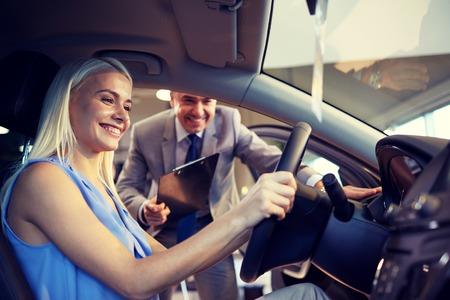 Foto de auto business, car sale, consumerism and people concept - happy woman with car dealer in auto show or salon - Imagen libre de derechos