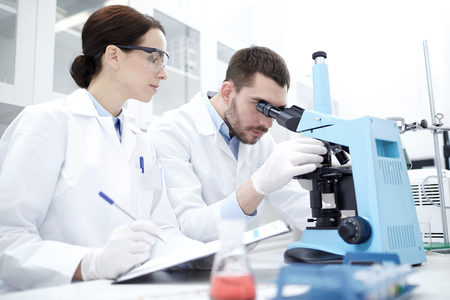 Foto de science, chemistry, technology, biology and people concept - young scientists with microscope making test or research in clinical laboratory and taking notes - Imagen libre de derechos