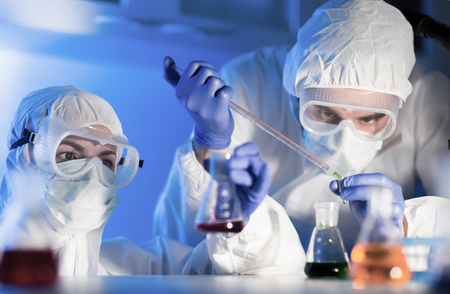 Foto de science, chemistry, biology, medicine and people concept - close up of young scientists with pipette and flasks making test or research in clinical laboratory - Imagen libre de derechos