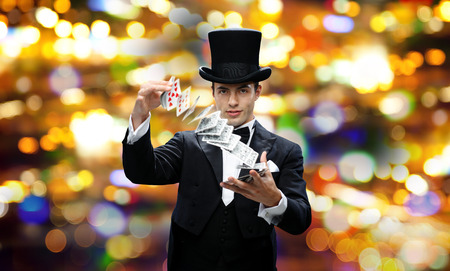 Photo for magic, gambling, casino, people and show concept - magician in top hat showing trick with playing cards over nigh lights background - Royalty Free Image