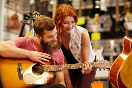 Photo for music, sale, people, musical instruments and entertainment concept - happy couple of musicians with guitar at music store - Royalty Free Image