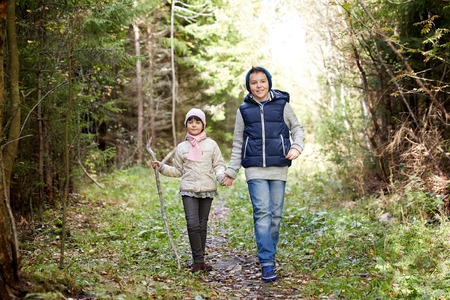 childhood, hiking, family, friendship and people concept - two happy kids walking along forest path