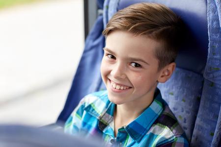 Photo pour transport, tourism, road trip and people concept - happy boy sitting in travel bus or train - image libre de droit