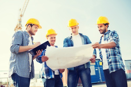 Foto per business, building, teamwork and people concept - group of smiling builders in hardhats with clipboard and blueprint outdoors - Immagine Royalty Free