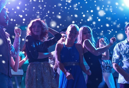 Foto de new year party, holidays, celebration, nightlife and people concept - group of happy friends dancing in night club and snow effect - Imagen libre de derechos