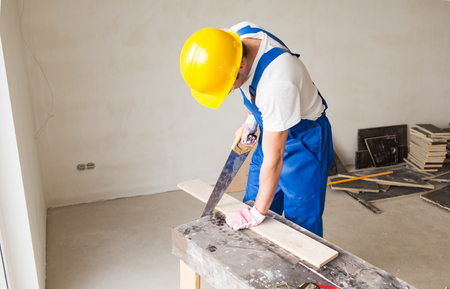 Photo pour building, carpentry, repair, teamwork and people concept - close up of builder with arm saw sawing board on table - image libre de droit