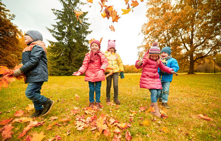 Photo pour childhood, leisure, friendship and people concept - group of happy kids playing with autumn maple leaves and having fun in park - image libre de droit