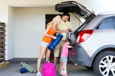 Photo pour transport, leisure, travel, road trip and people concept - happy family packing things into car at home parking - image libre de droit