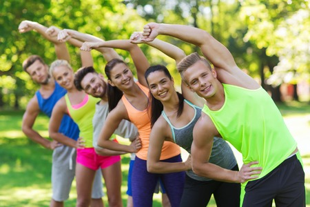Photo for fitness, sport, friendship and healthy lifestyle concept - group of happy teenage friends or sportsmen exercising and stretching at boot camp - Royalty Free Image