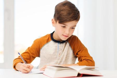 Foto de education, childhood, people, homework and school concept - student boy with book writing to notebook at home - Imagen libre de derechos