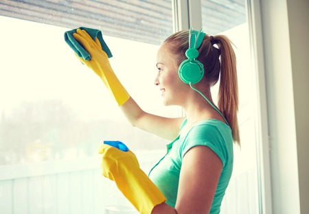 Foto de people, housework and housekeeping concept - happy woman in headphones listening to music and cleaning window with cleanser at home - Imagen libre de derechos