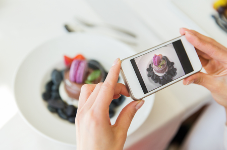 Foto de people, holidays, technology, food and lifestyle concept - close up of woman with smartphone taking picture of dessert at restaurant - Imagen libre de derechos