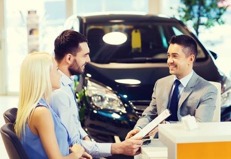 Photo pour auto business, sale and people concept - happy couple with dealer buying car in auto show or salon - image libre de droit