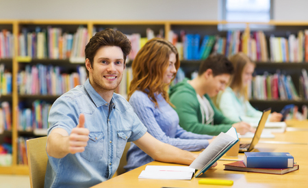 Foto de people, knowledge, education and school concept - happy student boy with books preparing to exam in library and showing thumbs up gesture - Imagen libre de derechos
