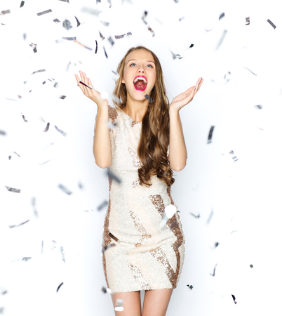 Photo pour people, holidays, emotion and glamour concept - happy young woman or teen girl in fancy dress with sequins and confetti at party - image libre de droit